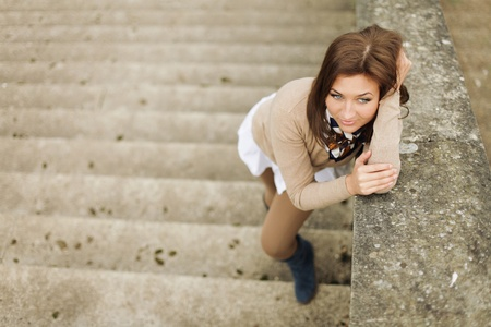 beautiful young woman posing on stairs photo