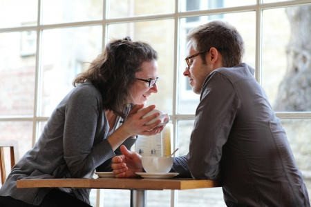couple talking: beautiful young couple drinking coffee in cafe Stock Photo