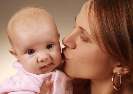 young mother kissing her child photo
