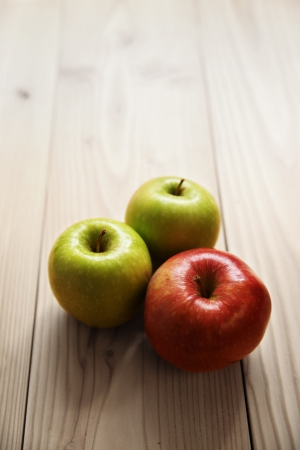 gala and two granny smith apples on wooden table Standard-Bild