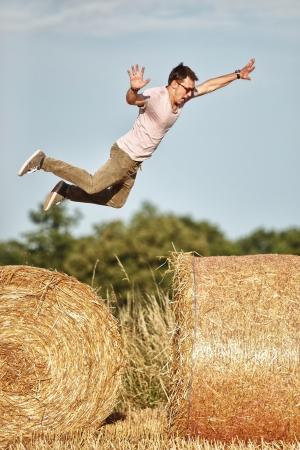 jumping fence: chico saltando por encima de los rollos de heno Foto de archivo