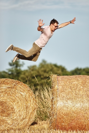 guy jumping over the hay rolls photo