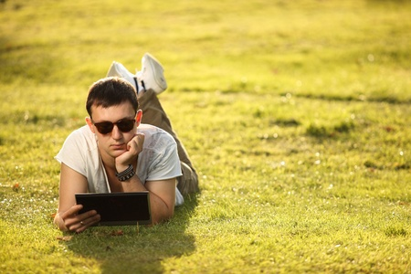 handsome student lying on the lawn with tablet