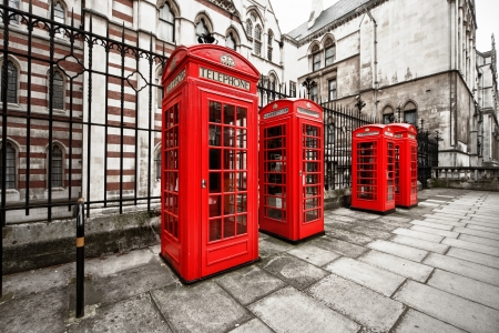 pay wall: horizontal shot of four red phone boxes on London