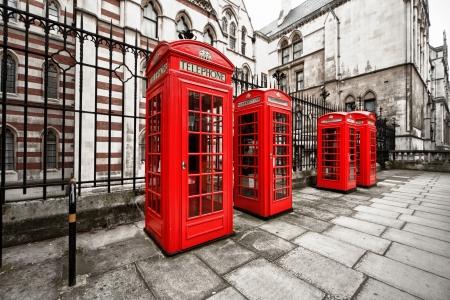 urban colors: tiro horizontal de cuatro cabinas telefónicas rojas en Londres