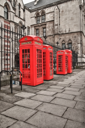 four red telephone boxes on the street of London photo