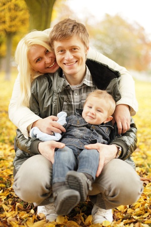 vertical image: funny family in autumn park