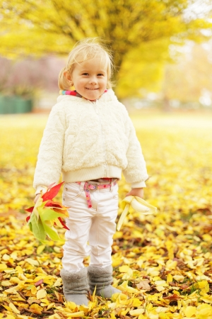 funny little girl in yellow autumn park