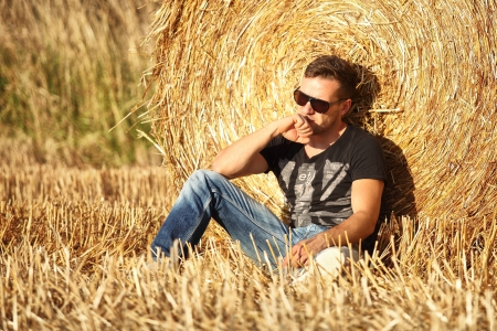 man field: handsome man leaning against golden hay roll