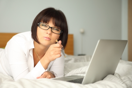 attractive woman lying on bed with laptop