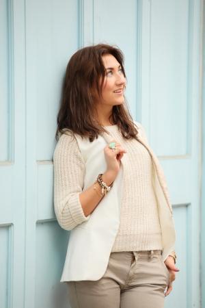 attractive woman standing against blue door