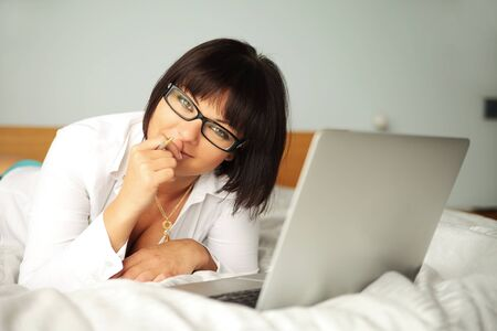 beauty with laptop lying on bed photo