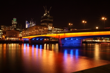 London Bridge lit with orange and blue at night