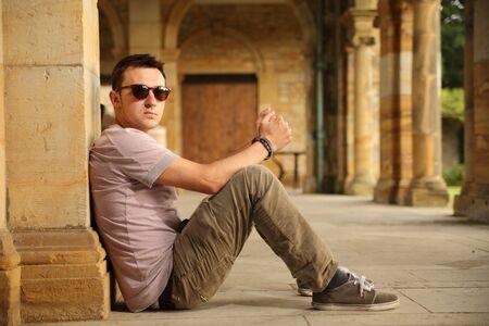 young stylish guy sitting on pavement Standard-Bild