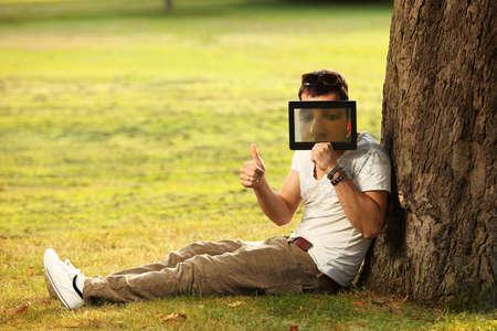 Junger Mann herumalbern mit Tablette im Park Standard-Bild - 18060327