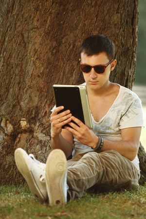 guy with tablet under tree