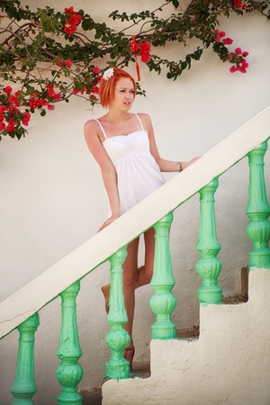 red haired young woman standing on stairs of greek house Standard-Bild