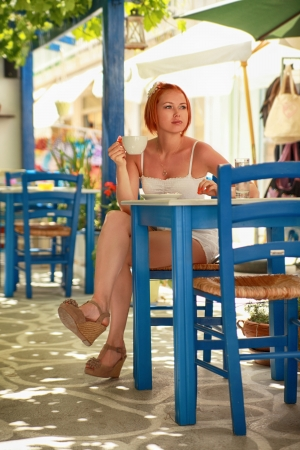 beautiful redhaired woman having a cup of coffee in the street cafe