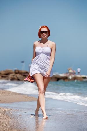 beauty in white walking along the sea shore photo
