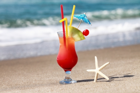 bright red cocktail on the sea shore
