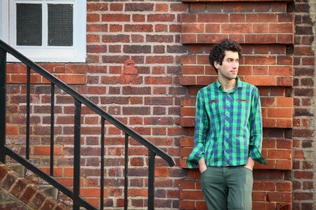 young handsome model posing against brick wall