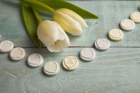 Reihe von Süßigkeiten auf blauen Holz taable von denen sagt, Be Mine und Tulpen Standard-Bild - 25962215