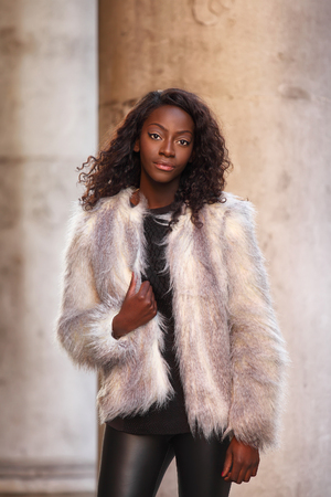 beautiful african woman dressed in fur coat posing outdoors photo