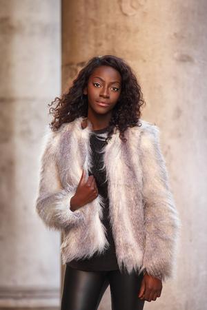 Schöne afrikanische Frau im Pelzmantel posiert im Freien gekleidet Standard-Bild - 25962219