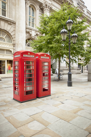 two K2 red phone booths on one of London's streets