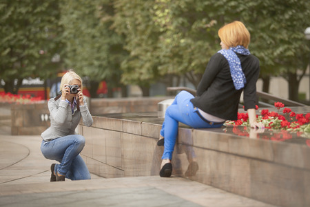 blonde lady taking pictures of redhaired model in park