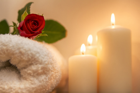 red rose, burning candles and towels in spa composition Standard-Bild