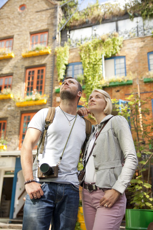 tourist couple with cameras against Neal's Yard's colourful buildings