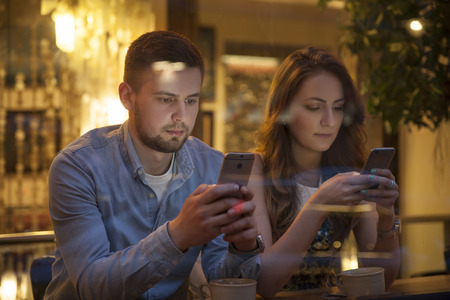couple in cafe addicted to their smartphones