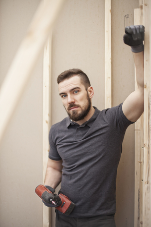 builder posing against plasterboard partition