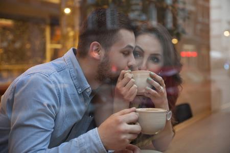 hombre tomando cafe: disparo a través del café joven pareja, beber café en el escaparate