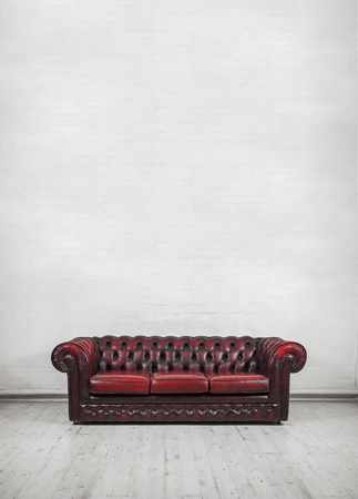 chesterfield: oxblood red vintage chesterfield sofa against painted brick wall place text or canvas on wall