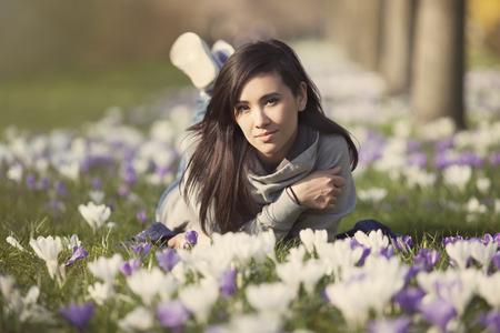 beautiful young woman lying on crocus lawn