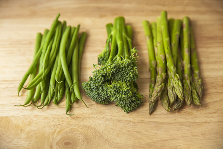 healthy green vegetables on wooden chopping board