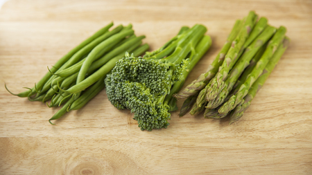 broccoli fine beans and asparagus on wooden chopping board