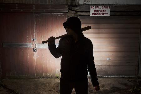 hoodlum: silhouette of youngster in hoodie standing in shadow against garage doors