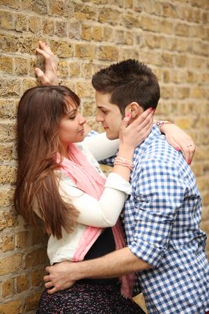 벽돌 벽에 아름다운 여자를 포옹 잘 생긴 젊은 남자