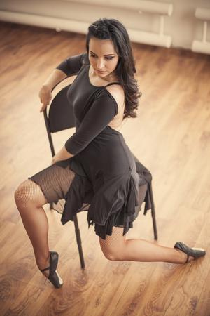 donna che balla: giovane ballerina in posa sulla sedia in studio di danza
