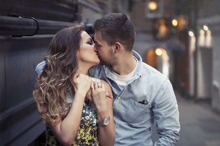 true love: beautiful couple kissing on one of Londons streets