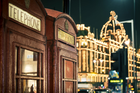 knightsbridge: two red phone boxes at night in Knightsbridge against lit shopping centre