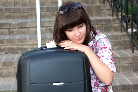 Beautiful girl sad sitting on the stairs with a suitcase photo