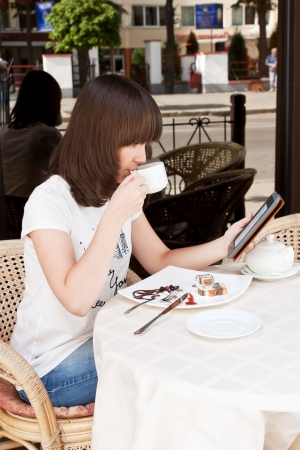 Beautiful girl in a summer cafe reading a book and drinking tea photo