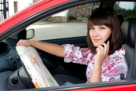 Beautiful girl in the car on the road map looks photo