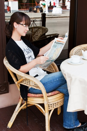 Beautiful girl in a summer cafe drinking tea and reading the newspaper photo