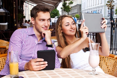 Girl with guy in cafe used tablet computer photo