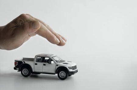 Male hand in a protective gesture, holding hand over a toy car on a white background. Stock Photo